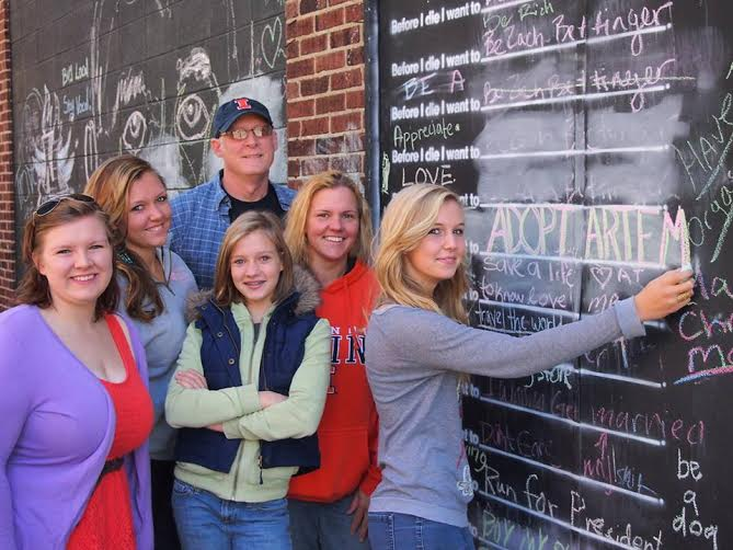 "The Burnett family wrote ""adopt Artem"" on the Before I Die wall in Champaign. Artem is the Ukranian orphan the family hosted last summer, who they are now trying to adopt. Photo provided"