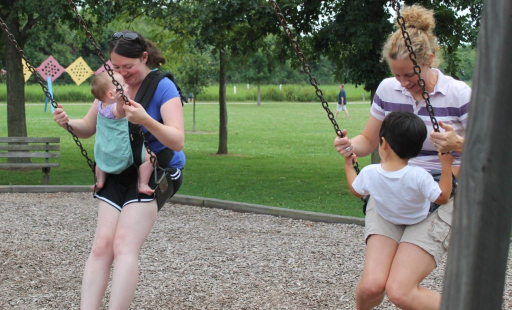 Parents swinging with children at Meadowbrook Park