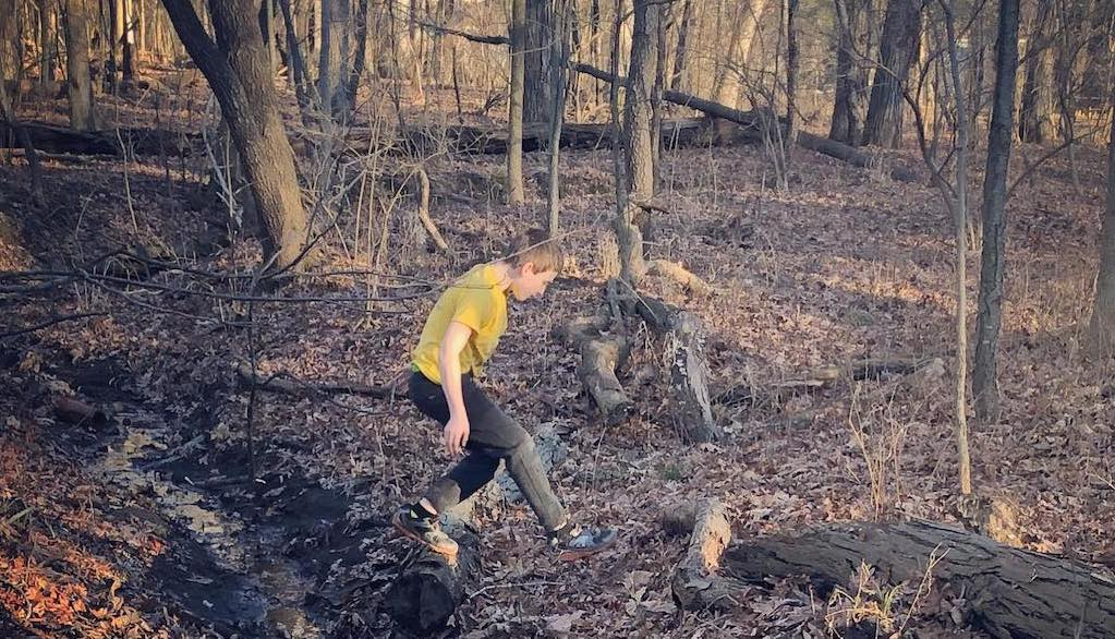 Boy in short sleeves runs through wooded area coated with dead leaves