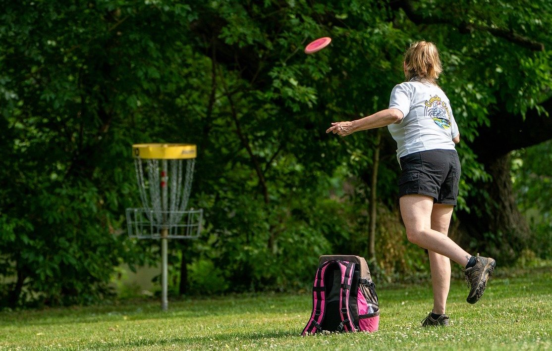 Woman throwing disc at disc golf target