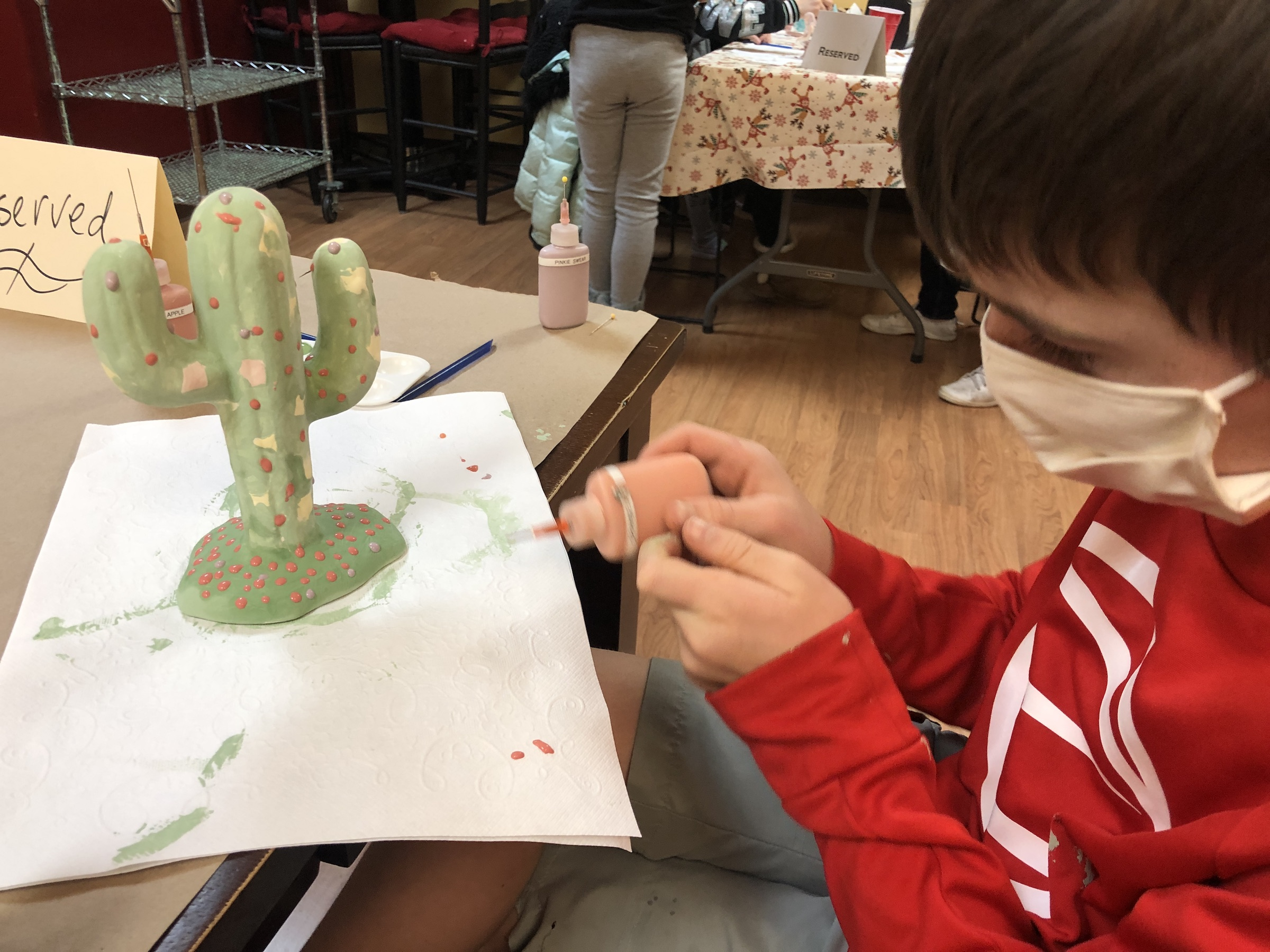 child painting at pottery place